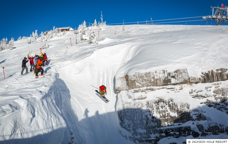 A skier in red drops into a steep slope at the top of a mountain