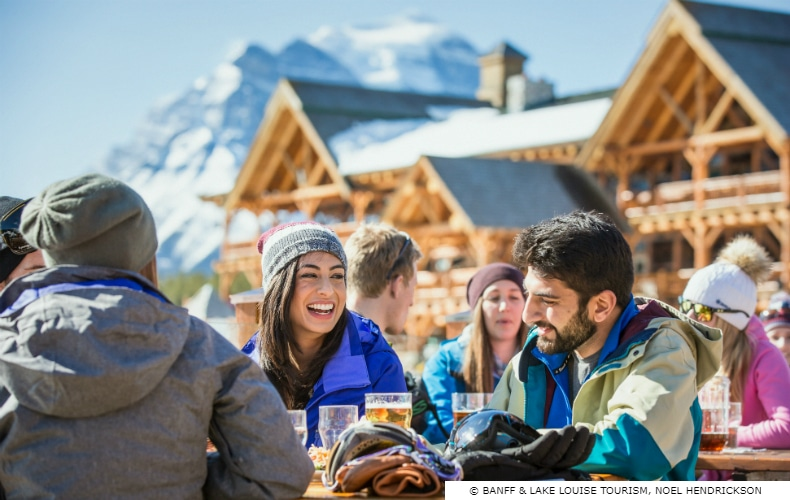 A smiling, laughing woman and bearded man enjoy drinks with frinds after a long day of skiing