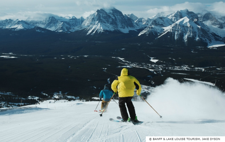 Skier in yellow and a skier in blue descend one of the many runs at Lake Louise Ski Resort in Canada's Rocky Mountains
