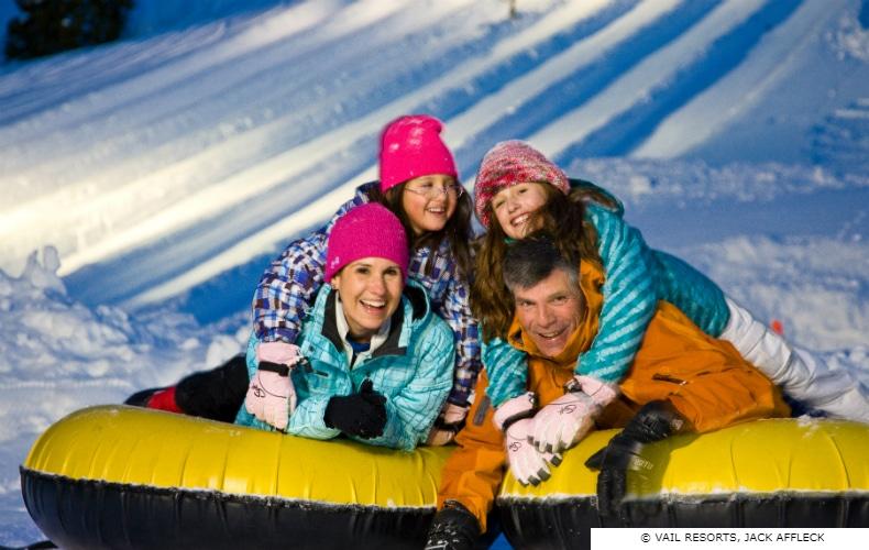Happy family at the end of a ride in an inflatable at a snow field