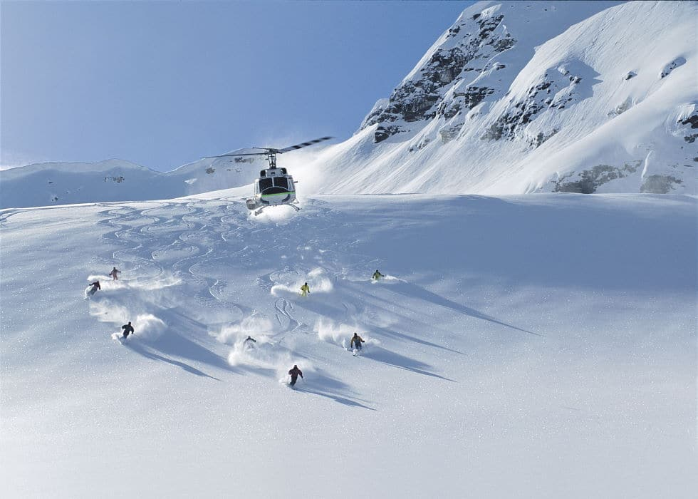Skiers descending Panorama Mountain with a helicopter in the air above them
